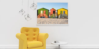 Composite image of yellow armchair by table against blank picture frame Stock Image