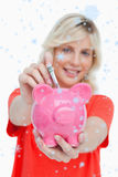 Composite image of young blonde woman putting notes into a pink piggy bank Stock Photos