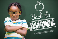 Composite image of young boy standing with arms crossed. Young boy standing with arms crossed against back to school Stock Photography