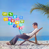 Composite image of young businessman on his beach chair using his laptop Stock Photo