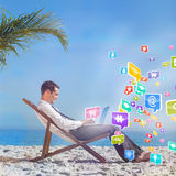 Composite image of young businessman on his beach chair using his laptop Stock Photos