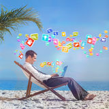 Composite image of young businessman on his beach chair using his laptop Royalty Free Stock Photos