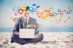 Composite image of young businessman with legs crossed typing on his laptop Royalty Free Stock Photography