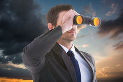 Composite image of young businessman looking through binoculars Royalty Free Stock Photo