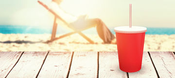 Composite image of young businessman resting on his deck chair using his tablet. Young businessman resting on his deck chair using his tablet against red cup Royalty Free Stock Image