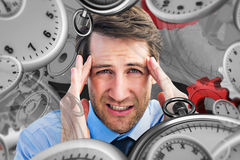 Composite image of young businessman with severe headache Royalty Free Stock Images
