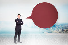 Composite image of young businessman standing cross-armed with speech bubble royalty free stock image