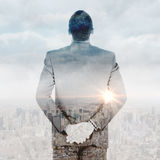 Composite image of young businessman standing with hands behind back Royalty Free Stock Photography