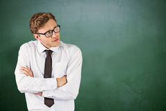 Composite image of young businessman thinking with arms crossed Stock Photography