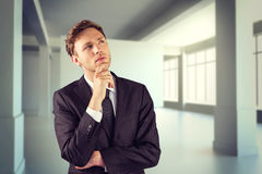 Composite image of young businessman thinking with hand on chin Royalty Free Stock Photography