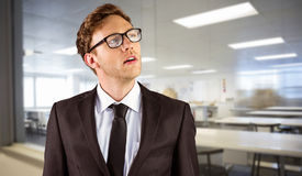 Composite image of young businessman thinking and looking up. Young businessman thinking and looking up against empty class room Stock Images