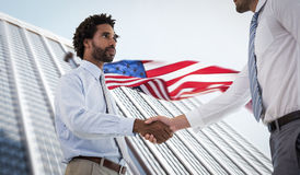 Composite image of young businessmen shaking hands in office Royalty Free Stock Photo