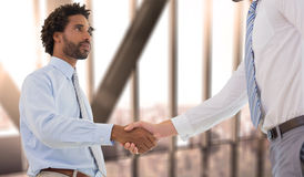 Composite image of young businessmen shaking hands in office Stock Photography