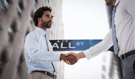 Composite image of young businessmen shaking hands in office Royalty Free Stock Image