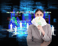 Composite image of young businesswoman hiding her face behind bank notes Stock Images
