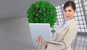 Composite image of young businesswoman with laptop. Composite image of confident young businesswoman with laptop Royalty Free Stock Photo