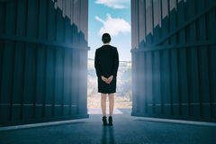 Composite image of young businesswoman standing with hands behind back 3d stock photography