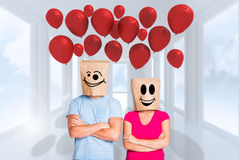 Composite image of young couple with bags over heads Stock Image