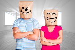 Composite image of young couple with bags over heads Stock Photo