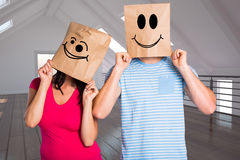 Composite image of young couple with bags over heads Royalty Free Stock Image