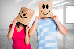 Composite image of young couple with bags over heads Stock Images