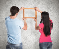 Composite image of young couple hanging a frame Royalty Free Stock Images