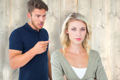 Composite image of young couple having an argument. Young couple having an argument against pale wooden planks Stock Photography