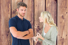 Composite image of young couple having an argument. Young couple having an argument against wooden planks background Stock Images