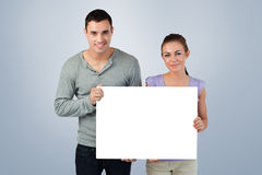 Composite image of young couple holding banner together Stock Image