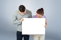 Composite image of young couple holding banner together and looking down Stock Image