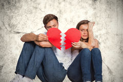 A Composite image of young couple holding broken heart. Young couple holding broken heart against grey background Royalty Free Stock Photos