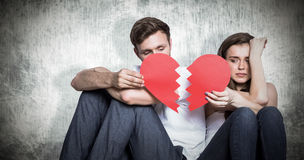 Composite image of young couple holding broken heart stock images