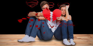 Composite image of young couple holding broken heart. Young couple holding broken heart against red hearts floating Stock Photography