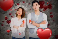 Composite image of young couple holding broken heart 3D. Young couple holding broken heart against love heart pattern 3D Royalty Free Stock Photography