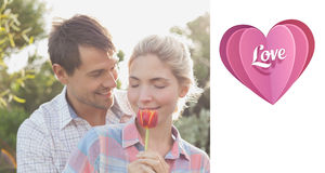 Composite image of young couple holding a flower in park Stock Photography