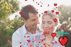 Composite image of young couple holding a flower in park. Young couple holding a flower in park against valentines day greeting royalty free stock photo