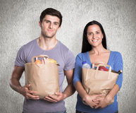 Composite image of young couple holding grocery bags Royalty Free Stock Photography