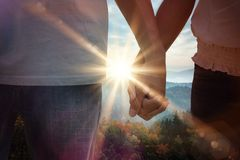 Composite image of young couple holding hands in the park royalty free stock photo