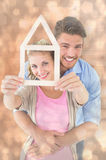 Composite image of young couple hugging and holding house outline Royalty Free Stock Image