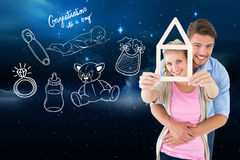 Composite image of young couple hugging and holding house outline Stock Photos