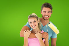 Composite image of young couple hugging and holding paint roller Stock Images