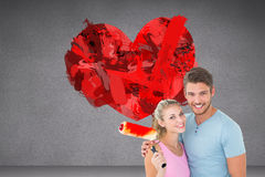 Composite image of young couple hugging and holding paint roller Stock Photography