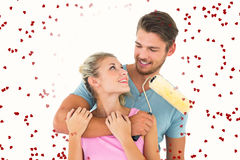 Composite image of young couple hugging and holding paint roller. Young couple hugging and holding paint roller against red love hearts royalty free stock image