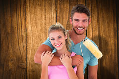Composite image of young couple hugging and holding paint roller Royalty Free Stock Images