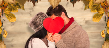 Composite image of young couple kissing behind red heart Royalty Free Stock Photos