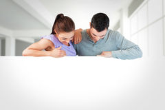 Composite image of young couple looking down a wall Royalty Free Stock Image