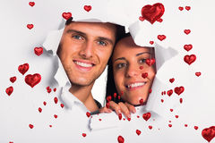 Composite image of young couple looking through paper rip Royalty Free Stock Photos