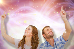 Composite image of young couple looking up and smiling Stock Images