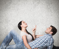 Composite image of young couple lying on floor smiling Stock Images