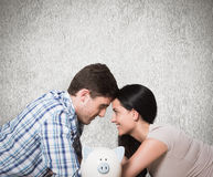 Composite image of young couple lying on floor smiling with piggy bank Stock Image